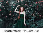 Stock photo the red haired girl in a long dress and vintage green hat posing against a background of peach 448525810