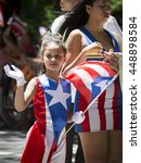 Small photo of NEW YORK - JUNE 12 2016: A young beauty queen wearing a Puerto Rican flag dress and jeweled tiara waves to the crowd at the 59th National Puerto Rican Day Parade on 5th Ave in NYC, June 12 2016.