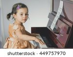 Little girl is reading notes and practicing piano - stock photo