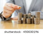 businesswoman put coins to... | Shutterstock . vector #450030196