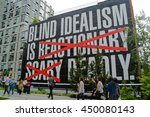 Small photo of 22 May 2016- Tourists and locals walk past sign with text: blind idealism is reactionary scary deadly, with certain words crossed out in large red crosses
