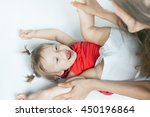 Small photo of Funny baby girl doing exercise and yoga with her happy mother on a white bed. Newborn looking at the camera and smiling. Mothercare is most important in baby life