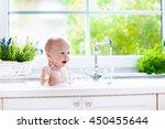 baby taking bath in kitchen... | Shutterstock . vector #450455644