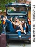 two girls posing in car.... | Shutterstock . vector #450530428