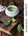 Small photo of Vintage ceramic bowl with broccoli mashed and aioli sauce, served with sackcloth rag on wood chopping board over old wooden background. Rustic style.
