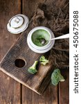 Small photo of Vintage ceramic bowl with broccoli mashed and aioli sauce, served with spoon and sackcloth rag on wood chopping board over old wooden background. Rustic style. Flat lay