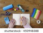 hand holds a pencil on desktop... | Shutterstock . vector #450948388