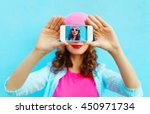 Small photo of Woman makes self-portrait on smartphone view screen over colorful blue background