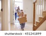 Family Carrying Boxes Into New...