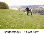 Stock photo mature couple taking golden retriever for walk 451257394