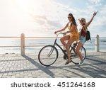 Joyful Young Women Riding A...