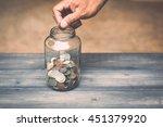 hand drops money into a glass... | Shutterstock . vector #451379920