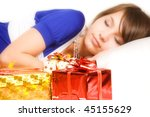 girl sleep near her gifts, focus on gifts - stock photo