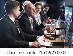 Small photo of Elderly man speaking during a conference, accompanied by his colleagues