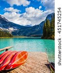 Small photo of The concept of active tourism and vacation. Emerald Lake in the Canadian Rockies. Shiny red kayaks are dried upside down