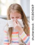young girl blowing her nose. | Shutterstock . vector #451804069