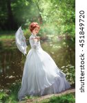 Small photo of Beautiful red haired girl in white long vintage dress and lace umbrella standing near river.Pretty tenderness model with perfect wedding hairstyle dreaming and looking afar.Art work and fairy tail