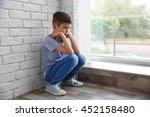 sad boy sitting near window | Shutterstock . vector #452158480