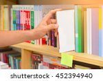 hand of man selecting a book... | Shutterstock . vector #452394940