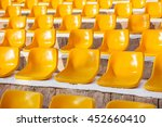 Small photo of Stone steps with yellow plastic seats. Empty stools without people. Concept photo - absence of audience.
