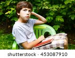 Bored Preteen Boy With Book Sit ...