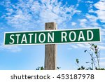Metal Green Station Road Sign on Wooden Post in Summer - stock photo