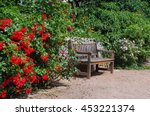 Stock photo tranquil garden bench surrounded by blossom bushes 453221374