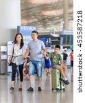 Small photo of BEIJING-JULY 13, 2016. Young couple with boy on a suitcase at Beijing Capital International Airport, Terminal 3, with 986,000 square meter the second largest airport terminal building in the world.