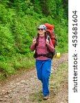 Happy Woman Hiker Trekking On...