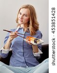 smiling young woman eating... | Shutterstock . vector #453851428