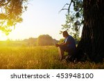 aged man is sitting beneath a... | Shutterstock . vector #453948100