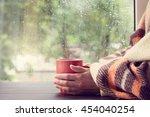 big red mug in the hands thrown ... | Shutterstock . vector #454040254
