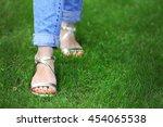 female feet in sandals on green ... | Shutterstock . vector #454065538