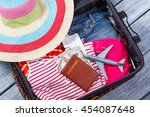 Small photo of Suitcase with clothes and passport. Toy plane and beach hat. Luggage on wooden shelf. Airplane ticket for summer trip.