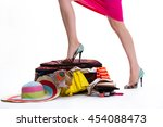 lady's leg on filled suitcase.... | Shutterstock . vector #454088473