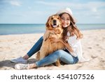 Stock photo cheerful pretty young woman in hat sitting and hugging her dog on the beach 454107526