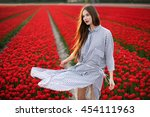 Stock photo beautiful young woman in striped dress standing in a red tulips field at sunset 454111963