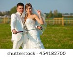 Small photo of Groom holds a golf mashy posing with a bride