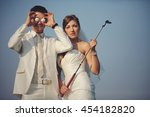 Small photo of Groom holds golf balls in the front of his eyes while bride holds a mashy