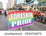 Small photo of TORONTO, CANADA - JULY 3, 2016: Marcher holding rainbow coloured FORESKIN PRIDE sign at Toronto Pride Parade.