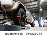 Small photo of Tire clamped with aligner undergoing auto wheel alignment in garage. Electronic tuning of car