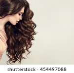 Small photo of Brunette girl with long and shiny wavy hair . Beautiful model with curly hairstyle