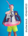 Funny young businessman in suit with beach accessories - stock photo