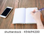 a young woman is writing in... | Shutterstock . vector #454694200