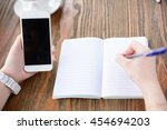 a young woman is writing in... | Shutterstock . vector #454694203