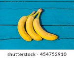 three ripe bananas on a blue... | Shutterstock . vector #454752910