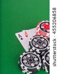 Small photo of photo of aces pair, red and black casino chips on green table