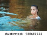 Small photo of Portrait of a woman in the water, she in a dress and all wet.