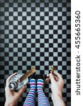 Small photo of Alice in wonderland. Background. A key and a potion in hands against a chess floor