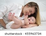 mother and baby daughter on bed | Shutterstock . vector #455963734
